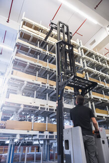 Worker operating forklift in factory warehouse - DIGF02320