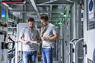 Two men in automatized high rack warehouse looking at tablet - DIGF02329