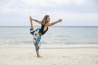 Woman practicing yoga on the beach - MOMF00164