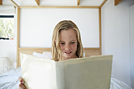 Portrait of content little girl reading a book at home - SRYF00254