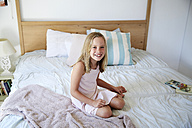 Portrait of smiling little girl sitting on bed at home - SRYF00257