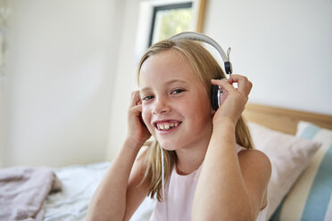 Portrait of smiling little girl listening music with headphones at home - SRYF00260
