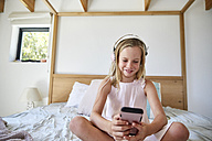 Smiling little girl sitting on bed at home while listening music with headphones - SRYF00263