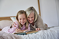Little girl lying on the bed with her grandmother reading a book - SRYF00275