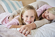 Portrait of happy little girl lying on the bed with her grandmother - SRYF00278