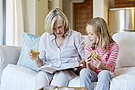 Grandmother and granddaughter sitting side by side on the couch looking at a book - SRYF00299