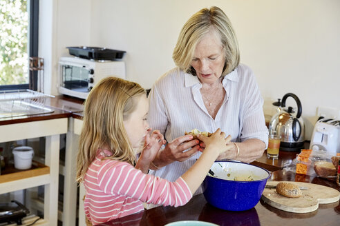 Grandmother and granddaughter preparing food in the kitchen - SRYF00302