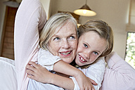 Portrait of smiling little girl hugging her grandmother - SRYF00308