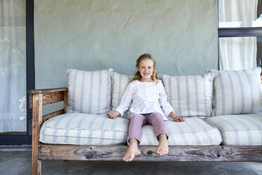 Portrait of smiling blond little girl  sitting on couch oo the terrace - SRYF00323