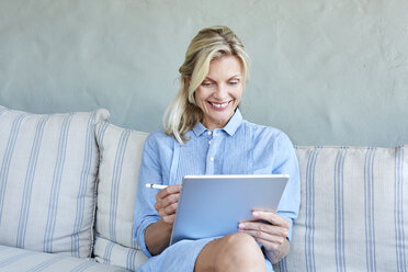 Portrait of smiling blond woman sitting on couch looking at tablet - SRYF00335