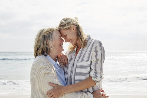 Senior woman and her adult daughter standing on the beach, embracing - SRYF00347