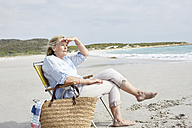 Senior woman sitting on the beach, looking at distance - SRYF00356
