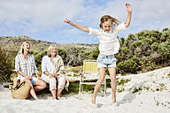 Mother, daughter and grandmother spending a day at the beach, girl jumping for joy - SRYF00365