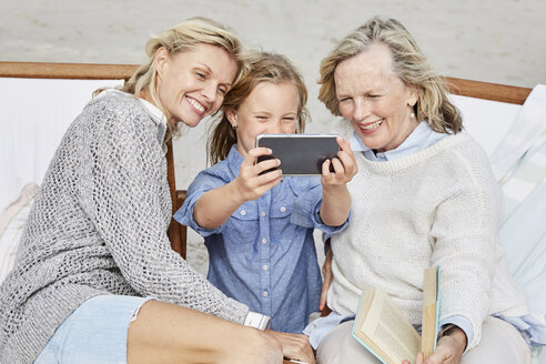 Mother, daughter and grandmother taking smartphone selfies on the beach - SRYF00374