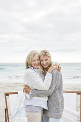 Mother and daughter embracing on the beach - SRYF00383