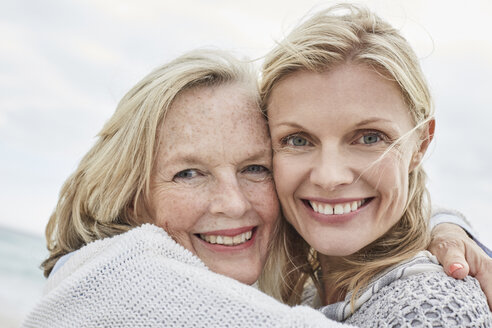Mother and daughter embracing on the beach - SRYF00386