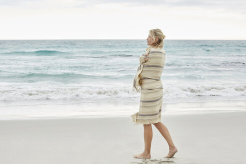 Mature woman enjoying the sea, wrapped in a blanket - SRYF00389