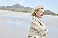 Mature woman enjoying the sea, wrapped in a blanket - SRYF00395