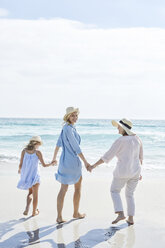 Mother, daughter and grandmother walking by the sea, rear view - SRYF00407