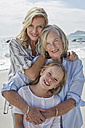 Mother, daughter and grandmother embracing on the beach - SRYF00425