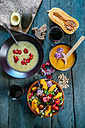 Bowls of creamed pumpkin soup and cream of avocado soup garnished with edible flowers - KIJF01434