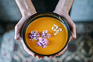 Man's hands holding creamed pumpkin soup garnished with edible flowers, close-up - KIJF01437