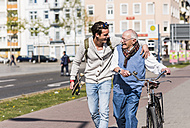 Happy senior man with adult grandson in the city on the move - UUF10414