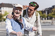 Happy senior man with adult grandson in the city on the move - UUF10417