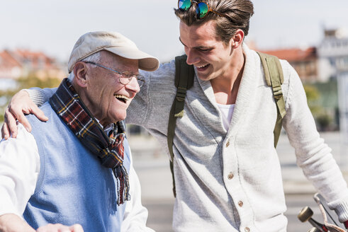 Happy senior man with adult grandson in the city on the move - UUF10420