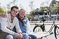 Portrait of happy senior man with adult grandson sitting on a bench - UUF10423