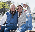 Senior man and adult grandson on a bench taking a selfie - UUF10429