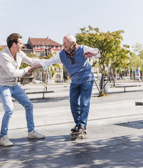 Adult grandson assisting senior man on skateboard - UUF10435