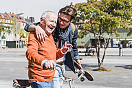 Happy senior man with adult grandson in the city on the move - UUF10438