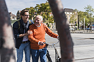 Happy senior man with adult grandson in the city on the move - UUF10441