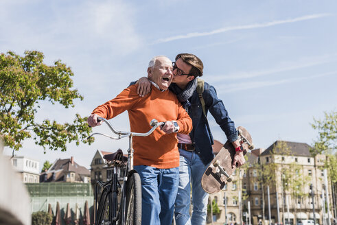 Adult grandson kissing happy senior man in the city - UUF10444