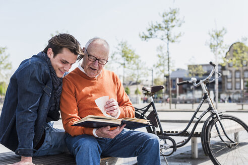 Senior man and adult grandson on a bench looking at photo album - UUF10450