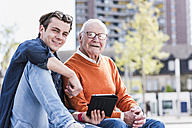 Portrait of smiling senior man and adult grandson with tablet - UUF10453