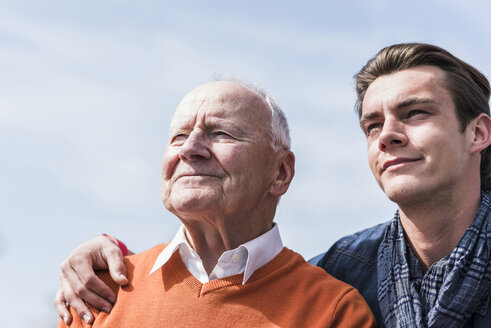Smiling senior man and adult grandson outdoors - UUF10456