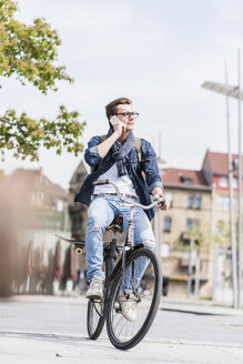 Young man with bicycle in the city talking on cell phone - UUF10462
