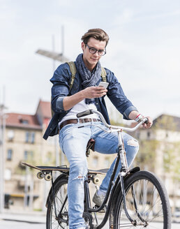 Young man with bicycle in the city using cell phone - UUF10465