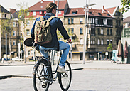 Young man holding skateboard riding bicycle in the city - UUF10471