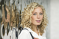 Portrait of smiling blond businesswoman with ringlets - PESF00525