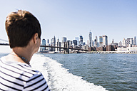 USA, New York City, woman on ferry with Manhattan skyline in background - UU10478