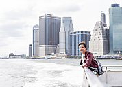 USA, New York City, woman on ferry with Manhattan skyline in background - UUF10481