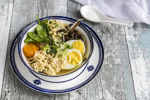 Bowl of ramen soup with spinach, carrot, boiled egg, bamboo sprouts and mushrooms - SARF03317