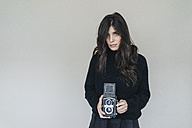 Dark-haired young woman holding vintage camera - KNSF01235