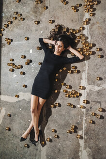 Smiling young woman lying on floor surrounded by Christmas baubles - KNSF01238