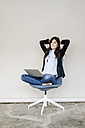 Smiling young businesswoman sitting on chair with laptop - KNSF01244