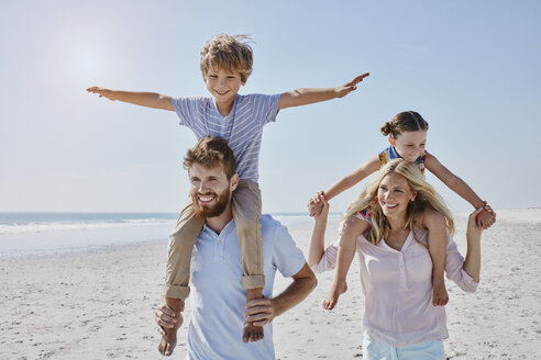 Happy family strolling on the beach - RORF00763