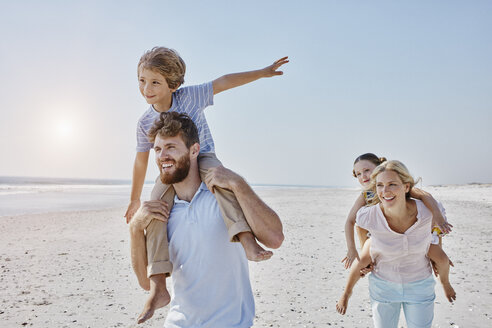 Happy family strolling on the beach - RORF00766